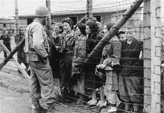 Women and children survivors in Mauthausen speak to an American liberator through a barbed wire fence. Mauthausen, Austria. May 05, 1945-May 07, 1945.  USHMM, National Archives and Records Administration (courtesy photo)
