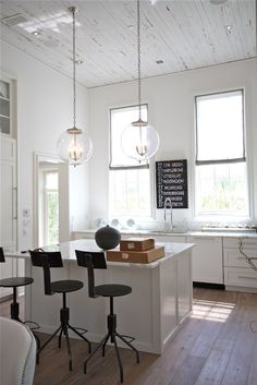 Rosemary Beach, FL - Amazing kitchen with whitewashed plank ceiling accented with clear glass globe pendants illuminating square island topp...