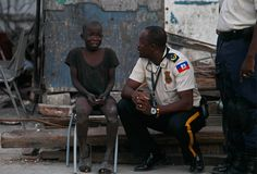 A child cries as he is questioned by police officer Carl Henry Boucher after he witnessed a gunfight in La Saline slum in Port-au-Prince, Tuesday, March 16, 2010. According to police at the scene, two police officers were ambushed and killed by suspected gang members who police believe may have escaped from prison after the Jan. 12 earthquake.