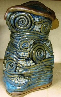 Maria N.- I really like this coil pot because of it's color. It has a metallic green and blue and gold and it looks very well put together. I also like the design and the variation of the spirals and coils and circles.