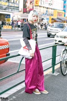 19-year-old Rio on the street in Harajuku wearing a No Doubt t-shirt with pink satin wide leg pants from Faith Tokyo, sneakers, and a septum ring. Full Look