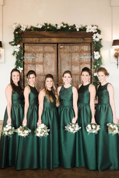 Group of women wearing winter wedding colors: dark green dresses and holding bouquets with greenery Satin Bridesmaids Gowns, Satin Bridesmaid Dresses, Wedding Dresses, Emerald Green Bridesmaid Dresses, Stone Bridesmaid Dress, Wedding Entourage Gowns, Alfred Sung Bridesmaid Dresses, Navy Blue Bridesmaids, Bridesmaid Outfit