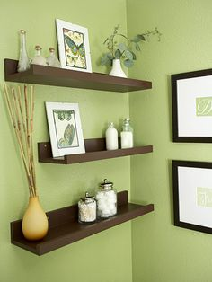 Floating shelves above the toilet add storage and display space to the room. Inspired by shelves spotted at a posh retail store, Kate painted budget-friendly pine shelves dark brown to match the dark wood in the bathroom. Inexpensive artwork adds a personal touch to the walls. Kate printed initials on her computer and then matted and framed them.