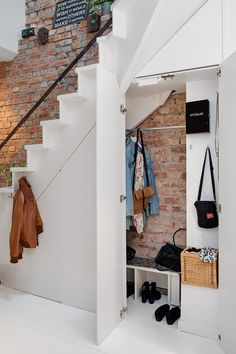 modern under stairs storages with wall hooks and bench with shoe racks underneath plus exposed brick wall smart ideas of storage under stairs emergency closet. under stairs. stairs line. Style At Home, Style Blog, Interior Exterior, Interior Design, Interior Ideas, Modern Interior, Hidden Storage, Extra Storage, Hidden Desk
