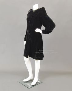 Black velvet coat with extended collar draping over cap shoulders, front button closure. Cream silk lining and self-buttons. C. 1930s. FRC 1996.01.012