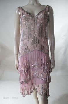 1920's pink chiffon flapper evening dress extravagantly embellished with silver beads and sequins, pink and white beads and pearly bugle beads. This classic drop-waist dress features a jazzy sleeveless silhouette cut daringly low front-and-back with three flirty flounces on the skirt and a hemline that's several inches longer in back