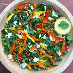 Asian Kale Salad  tonight! Kale, bell peppers, cauliflower, zucchini, carrot, green onion, and cilantro! Dressing is orange juice, tahini, and ginger