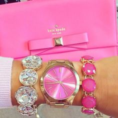 pink clutch and golden watch with shiny bling bling bracelets.