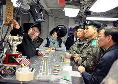 Lt. Cmdr. Dave Hecht gives distinguished visitors from United Nations Command a tour of flight deck control aboard the nuclear-powered aircraft carrier USS George Washington (CVN 73).