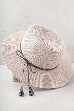 "Sunny days were made for the Sun Dweller Blush Straw Hat! This cute woven fedora has a grey, tying vegan suede band (with tassels), and floppy 3"" brim. 23"" interior circumference."