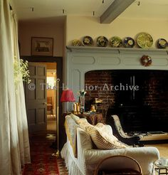 A collection of plates adorns the mantle above the large inglenook fireplace in this Welsh cosy sitting room.