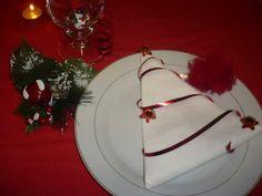 weiße Serviette zu Dreieck falten und mit rotem Band dekorieren