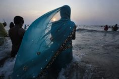 A woman prayed in the Arabian Sea during the Hindu festival Chhat Puja in Mumbai Monday. Devotees honor the sun god during the festival. (Vivek Prakash/Reuters)