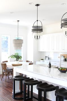 BECKI OWENS--A traditional white kitchen of marble, dark hardwood, and white cabinetry is updated with black modern accents and Urban Electrics Dover Bell Pendants.