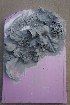 headstone. spray painted flowers and letters look like carved stone.