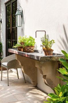 Chic garden features a concrete sink with corbels under a spigot faucet.