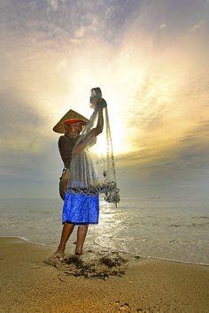 Fisherman at dawn, Bali, Indonesia.  Photo: Menjaring Asa Yang Tersisa via Flickr.