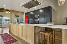 Contrasting red on black cabinetry fridge. Wooden island with a stone bench top and ceiling mounted extraction.