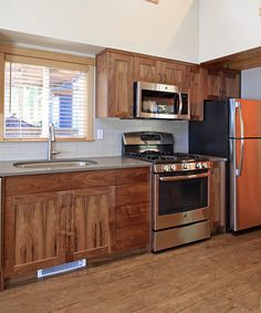 The kitchen includes beautiful walnut cabinetry, a freestanding range, dishwasher, and an apartment size refrigerator.