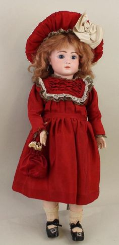 """21 1/2"""" J STEINER Bte S.G.D.G. PARIS FI RE A 13 ANTIQUE Blue paper weight eyes, closed mouth with parted lips, pierced ears, red mohair wig. Papier mache jointed body marked with paper label: Le Petite Parisian BeBe J. Steiner MEDAILLE D'OR PARIS 1889. 1-Pc. lower arms. Dressed in antique red silk dress with lace and metallic gold lace trims."""