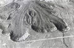 An aerial view shows the terminous of the Lava Park lava flow, erupted from a vent on the flank of Shastina lava dome on the NW flank of Mount Shasta about 9300 years ago. The blocky basaltic-andesite flow is about 6 km long and 110 m thick at its snout. The lava flow overlies a wide apron of pyroclastic-flow deposits erupted from Mount Shasta about 9700 years ago. The area shown is about 2000 m wide. The broad line crossing the photo near the bottom is Highway 97.