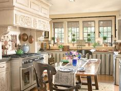 In the Family Kitchen, Acquisitions Cabinetry modifies its creme-colored Country Estate Collection to emulate the aesthetic and comfort of a European country kitchen. Colors in the tile mosaic over the stove are repeated in the fabric skirt below the counters.    - Veranda.com