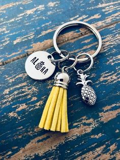 "Aloha Pineapple Key Ring This key ring contains a round silver aluminum disc hand stamped ""Aloha"" with a pineapple symbol for the ""o"" with a golden tassel and silver double-sided pineapple charm…MoreMore Cute Keychain, Tassel Keychain, Keychains, Cute Car Accessories, Jewelry Accessories, Pineapple Keychain, Cute Pineapple, Pineapple Girl, Cute Cars"