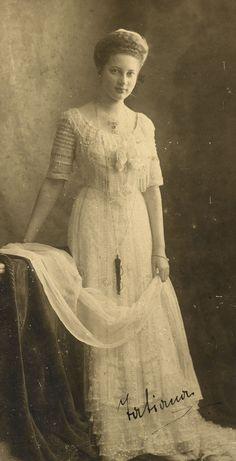 Princesa Tatiana Constantinovna, em 1909. Ela está de pé com o braço direito apoiado sobre a mesa ao lado dela para a esquerda. Ela está usando um vestido de cor clara embelezada e um longo colar e está segurando um pedaço de material de renda com as duas mãos. A fotografia é assinada com seu nome.