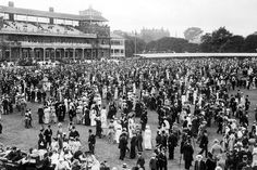 Well dressed spectators at a cricket match at Lords in July 1914 on the field in front of the main stand