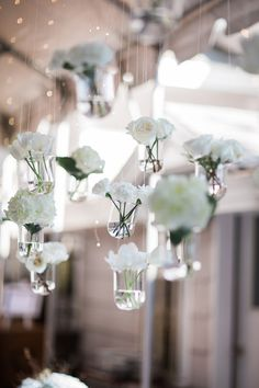 Elegant wedding reception decor idea - hanging white flowers in glass vessels {Michele Ashley Photography}