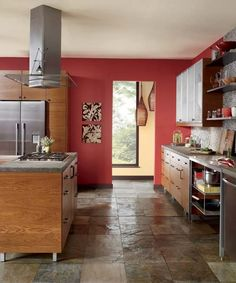 A fiery accent wall picks up the red tones in honey kitchen cabinetry. | Morocco Red UL110-4, @BEHR®