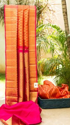 A beautiful orange kanchivaram silk with gold zari work throughout the body. The saree has an intricately woven border and pallu which elevate the piece