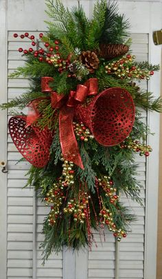This Christmas Swag is made with red ribbon, pinecones, bells, berries, and mixed pines. It measures approx. 26L x 15W x 9D. It is made on a pine base. This wreath will work inside or out with protective covering. It will have a limited life span if not protected from the elements.