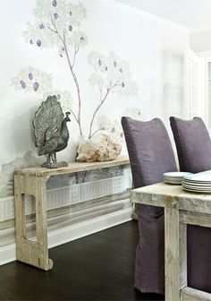 Whimsical dining room design with purple linen slip-covered slipper chairs, rustic wood dining table, reclaimed wood console table, iron peacock statue and tree wall mural. Dining Room Buffet, Console Table, Dining Rooms, Dining Table, Purple Dining Chairs, Wooden Beams Ceiling, Tree Wall Murals, Composite Adirondack Chairs, Slipper Chairs
