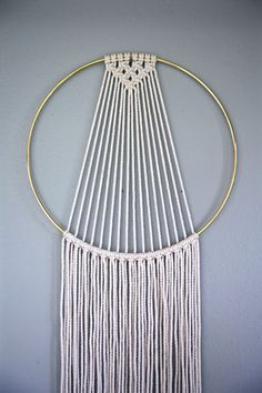 Dreamy handmade macrame wall hanging, made from 3mm natural white cotton rope and a 10 brass ring. Features a knotted design and long fringe.