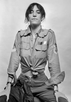 Studio portrait of Patti Smith wearing a US air force shirt, Amsterdam, Netherlands, October 1976