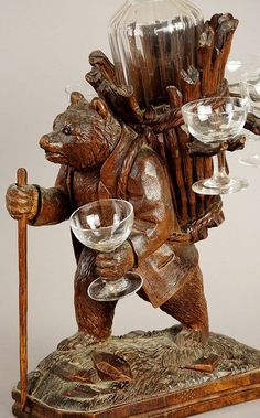 """""""Black Forest wooden carved bear, with walking cane. Holds a glass in one hand ,and carries a basket on his back to hold more glasses and a decanter... It is a """"liqueur stand"""""""
