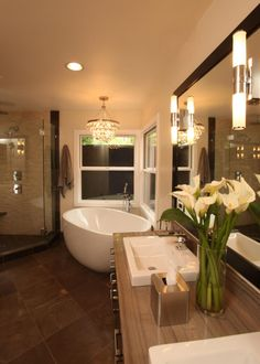 A crystal-tiered chandelier hangs above a freestanding tub in this contemporary bathroom, adding to the luxurious feel of the space. Textured mosaic tile in the shower echoes the lines of the brown tile flooring, while a linear stone counter on the vanity enhances the flow of the space. The room works in harmony to create a perfect retreat of personal extravagance.