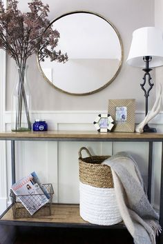 Sofa table with lavender , round mirror, rattan basket, wire basket, blanket storage. Neutral living room, chair rail, board and batten, simple, metal lamp. #afflink