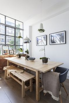 The use of solid wood benches and dining table, alongside hanging plants, make MADE customer Sonny's dining area look effortlessly Nordic. MADE.COM/Unboxed