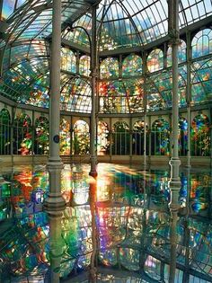 """Kimsooja, """"To Breathe - A Mirror Woman"""", 2006, an installation of translucent diffraction film on windows that create colorful light reflected by a mirrored floor, Palacio de Cristal, Parque del Retiro in Madrid, Spain."""