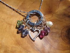 """GREAT MOTHERS DAY GIFT FOR MOM- SHE WILL LOVE IT!!  BEAUTIFUL FAMILY BIRTHSTONE CHARM NECKLACE WITH HEART....  Beautiful silver circle with the word """"Mother"""" dangles with any swarovski crystal birthstone charm or pearl..  Two Swarovski crystal birthstones and a silver heart are included in each order.... Each additional birthstone is only 2 dollars each.   http://www.etsy.com/listing/97099829/special-mother-with-heart-family  $18.00"""