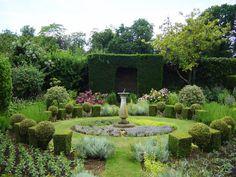 Circular garden, box and ball topiary hedge, central sundial, roses, symmetry