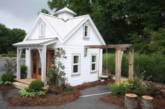 White and rustic accents. Seems like a display set up in parking lot. Tiny house, play house or garden shed?