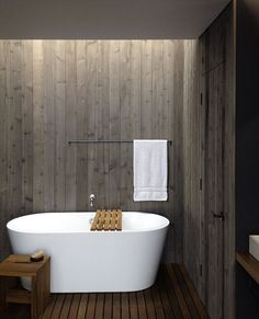 Such contrasts of textures, between the slatted teak floors, the smooth porcelain of the tub, and the grey walls that look like knotted wood. I love the light coming from the top of the wall and behind the ceiling drop, that washes the walls.