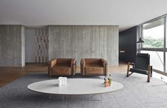 The concrete walls of this Brazilian home are warmed up by rich leather chairs, a textured area rug, oval coffee table, wood flooring and beautiful views.