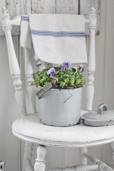 vintage chair and kitchen towel + enamel pot used as planter