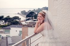 Bride with balcony view over Poole Harbour at Harbour Heights wedding photos. Photography by one thousand words wedding photographers