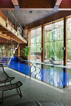 Near Moscow, this house designed by architect Olga Freiman has an electric blue pool within a double-height space that looks out through floor-to-ceiling glass windows.