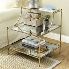 Emeline Side Table. With its stepped back glass shelves, our Emeline Side Table creates lots of storage and display in an airy, elegant design. The slender legs and curved arms are topped with button finials for a dressy finishing touch.  Emeline Side Table features:      Dressy antique foil finish     Hand crafted of iron     Antique Gold features     Antiqued Mirrored top and shelf     Antique Silver features     Clear glass top and shelf